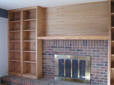 Hearth to ceiling oak bookcases were custom built to surround a fireplace. Adjustable shelves can accommodate a library collection of varied book sizes for the avid reader or scholar. Matching oak mantel and wall paneling integrate the appearance.
