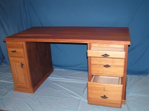 This solid mahogany desk was custom built with a pull-out writing surface, locking drawer for hanging files, and computer CPU storage space. Fancy drawer pulls, top edge beveling, and base moulding provide finishing touches.