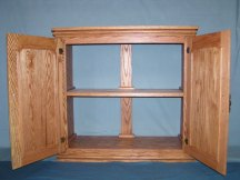 Open doors on this custom oak aquarium stand show the interior storage space including a fixed shelf
