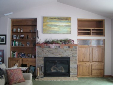 Custom built-in entertainment center in knotty alder, constructed to right of fireplace