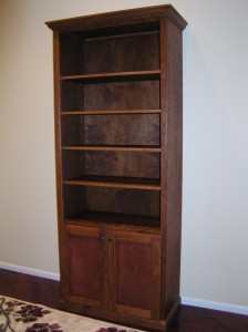 This cherry bookcase provides for storage in the base and adjustable shelves above to display books, family photos, or knick-knacks.