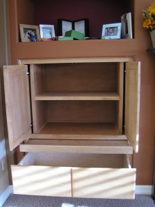 Open maple storage cabinet showing base drawer, pull-out shelf, and retracting doors around fixed shelf unit