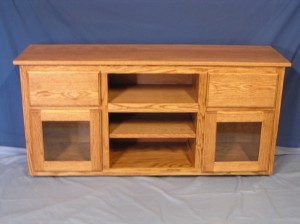 This custom-made oak TV / Stereo Console will support a flat screen TV, has space for components, and sports glass-front doors and storage drawers.